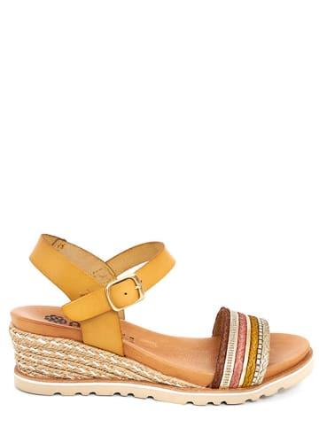 Abril Flowers Skórzane sandały w kolorze musztardowym ze wzorem na koturnie